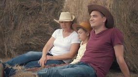 Gelukkige familiemoeder, vader, en zoon met een tabletzitting op het gebied, die op een hooi-broodje leunen Het concept gelukkig stock videobeelden