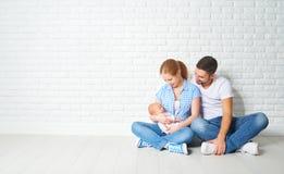Gelukkige familiemoeder, vader van een pasgeboren baby op vloer dichtbij blan Royalty-vrije Stock Afbeelding