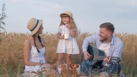 Gelukkige familieogenblikken, drinkt weinig leuk jong geitjemeisje melk van fles terwijl haar mooie ouders en jong papaspel lache stock videobeelden