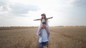 Gelukkige familieogenblikken, jonge vaderlooppas met weinig kindmeisje op zijn schouders dat gilt en zich het lachen verheugt en stock video