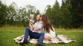Gelukkige familieouders die met baby tijdens picknick in park spelen stock video