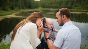 Gelukkige familieouders die met baby tijdens picknick in park spelen stock footage