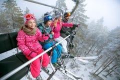 Gelukkige familieskiërs bij de skilift bij berg Stock Afbeeldingen