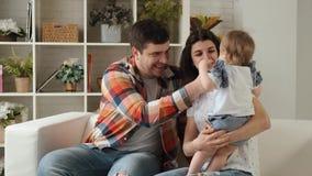 Gelukkige familiespelen met hun pasgeboren dochter samen in langzame motie stock video