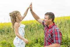 Gelukkige familievader en kinddochter op gele bloemen op aard in de zomer stock foto
