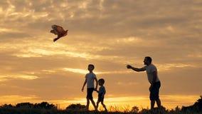 Gelukkige familievader en kinderen die in de weide met een vlieger in de zomer bij zonsondergang lopen stock footage