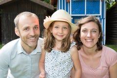 gelukkige familievader en moeder in openlucht met dochter jong kind in vrijetijdskleding stock afbeeldingen
