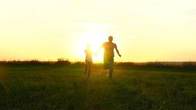Gelukkige familievader en zoon die over het groene gebied tegen de zonsondergangachtergrond lopen stock videobeelden
