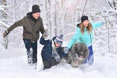 Gelukkige familievader, zoon, moeder en huisdier die in de winterpark lopen royalty-vrije stock afbeeldingen