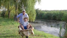 Gelukkige familievakantie in platteland, vaderdwazen rond met zijn zoon in kruiwagen dichtbij rivier met riet stock videobeelden