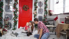 Gelukkige familiezitting en lezing een boek naast een prachtig verfraaide deur stock videobeelden