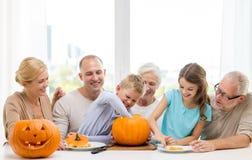 Gelukkige familiezitting met pompoenen thuis Stock Afbeeldingen