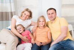 Gelukkige familiezitting op bank Stock Foto