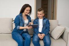 Gelukkige familiezitting op bank en thuis het gebruiken van digitale tablet Royalty-vrije Stock Afbeeldingen