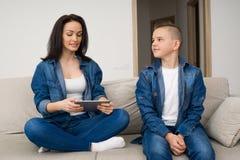 Gelukkige familiezitting op bank en thuis het gebruiken van digitale tablet Royalty-vrije Stock Afbeelding