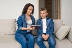 Gelukkige familiezitting op bank en thuis het gebruiken van digitale tablet stock afbeelding
