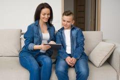 Gelukkige familiezitting op bank en thuis het gebruiken van digitale tablet stock fotografie