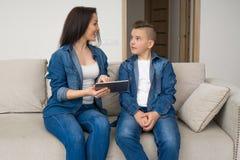 Gelukkige familiezitting op bank en thuis het gebruiken van digitale tablet royalty-vrije stock foto's