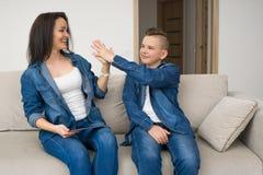 Gelukkige familiezitting op bank en thuis het gebruiken van digitale tablet stock afbeeldingen