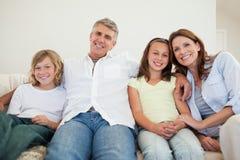 Gelukkige familiezitting op de bank Stock Foto