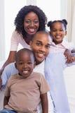 Gelukkige familiezitting op de laag samen stock foto's