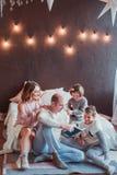 Gelukkige familiezitting op de vloer door het bed in het nieuwe jaarbinnenland De papa leest een boek De kinderen lachen Comforta stock fotografie