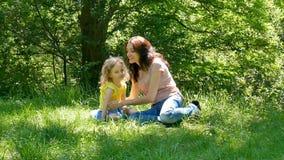 Gelukkige familiezitting op het groene gras in het park Weinig kinddochter die en haar moeder in openlucht koesteren kussen stock videobeelden
