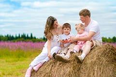 Gelukkige familiezitting op hooiberg in de zomer Stock Foto's