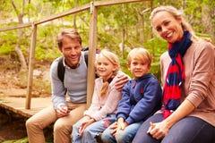 Gelukkige familiezitting op houten brug in een bos, portret Stock Foto