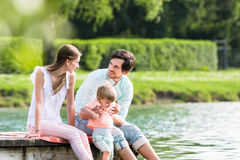Gelukkige familiezitting op pier op meer of vijver stock foto's