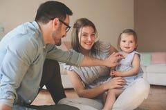 Gelukkige familiezitting op vloer met hun kleine baby Stock Afbeeldingen