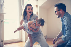 Gelukkige familiezitting op vloer met hun kleine baby Stock Fotografie