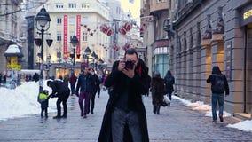 Gelukkige fotograaf die beelden nemen, terwijl de Mensen die door de straat van Knez Mihailova, de Hoofdstraat in Belgrado lopen stock videobeelden