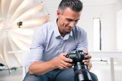 Gelukkige fotograaf die camera met behulp van Royalty-vrije Stock Afbeeldingen
