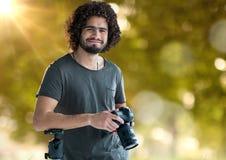 gelukkige fotograaf met camera op handen en vaag bos met erachter lichten en gloed royalty-vrije stock foto's