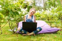 Gelukkige freelancer die in de tuin werken Schrijven, die in Internet surfen die laptop met behulp van Jonge en vrouw die ontspan royalty-vrije stock afbeelding