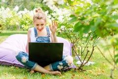 Gelukkige freelancer die in de tuin werken Schrijven, die in Internet surfen Jonge vrouw die aan de camera tijdens a golven stock foto