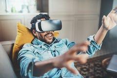 Gelukkige gebaarde Afrikaanse mens die van de virtuele hoofdtelefoon van werkelijkheidsglazen of 3d bril genieten terwijl het ont Stock Foto's