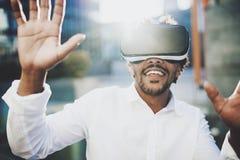 Gelukkige gebaarde Amerikaanse Afrikaanse mens die van de virtuele hoofdtelefoon van werkelijkheidsglazen of 3d bril genieten ter Royalty-vrije Stock Foto's