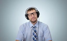 Gelukkige gebaarde mens die aan muziek met hoofdtelefoons luisteren stock foto's