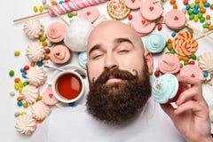 Gelukkige gebaarde mens het bijten roomcake die op witte achtergrond wordt ge?soleerd royalty-vrije stock foto