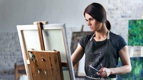 Gelukkige geconcentreerde mooie vrouwelijke schilder die tekenings van beeld in het middelgrote schot van de kunststudio genieten stock footage