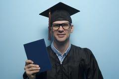 Gelukkige gediplomeerde mens met diploma in handen royalty-vrije stock afbeelding