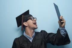 Gelukkige gediplomeerde mens met diploma in handen stock foto