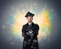 Gelukkige gediplomeerde met kleurrijke bokeglichten op de achtergrond stock foto's