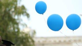 Gelukkige gediplomeerden die ballons houden alvorens hen, de traditie van studenten vrij te geven stock video