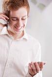 Gelukkige geek met twee mobiele telefoons royalty-vrije stock foto