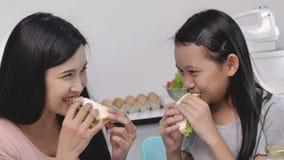 Gelukkige geglimlachte moeder en dochterzitting in de keuken en het maken van sandwiches stock videobeelden