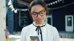 Gelukkige gemengde rastiener die moderne smartphone in openlucht in de straat gebruiken stock video