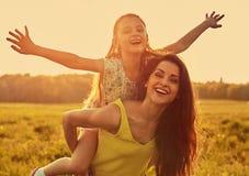 Gelukkige genietende van moeder die haar speels lachend jong geitjemeisje op achtergrond van de zonsondergang de heldere zomer ko stock afbeeldingen